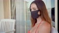 Portrait of beautiful dark haired young woman wearing protective medical face mask and sitting near home with reflected people in window. Safe and happy female practicing social distancing and 80269669