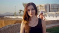Portrait cute woman with curved hairs standing in sea resort against background of european tourists and hotel. Female at evening 80269672
