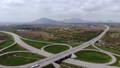 Aerial view of a suburban interchange with few moving vehicles. Suburban road infrastructure concept. Warm summer day against the background of the mountains 80313303