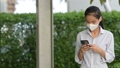 Woman wearing face mask to protect from coronavirus Covid-19 while using phone and taking selfie 80448084