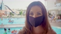 Woman in medical protective face mask in red bikini adheres to rules of social distance and standing against background of swimming pool in luxury resort with resting people during world wide corona 81206014