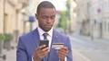 Outdoor African Businessman having Online Payment Success on Smartphone 81568246