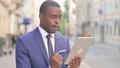 Outdoor African Businessman Celebrating on Tablet  81572231