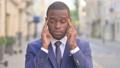 Outdoor African Businessman having Headache  81574372