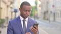Outdoor African Businessman using Smartphone  81574382