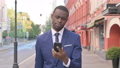 Walking African Businessman Reacting to Loss on Smartphone 81574396
