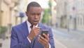 Outdoor African Businessman having Loss on Smartphone  81574407