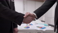 Close-up handshake of two Caucasian businessmen in office indoors. Unrecognizable men in black formal suits shaking hands in slow motion making agreement. Partnership and successful cooperation. 82046524
