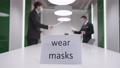 Wear masks message in business office with blurred Caucasian men in coronavirus face masks passing documents at background. Social distancing and Covid-19 prevention on pandemic outbreak. 82046525