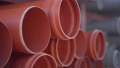 Close-up orange plastic pipes stack at warehouse. Industrial manufactured product lying in storage. No people, slow motion. 82125692