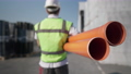 Live camera follows orange plastic pipes with blurred man in uniform carrying warehouse product. Back view of unrecognizable employee walking in slow motion with cargo for shipping outdoors. 82125693
