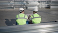 Back view of professional architect and engineer sitting at warehouse outdoors analyzing blueprint. Middle Eastern and Caucasian men talking thinking on project in slow motion in sunshine. 82125694