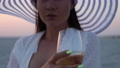 Elegant woman with glass of wine resting on beach at sunset 82175878