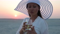 Elegant woman with glass of wine resting on beach at sunset 82175884