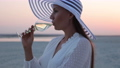 Elegant woman with glass of wine resting on beach at sunset 82175887