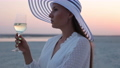 Elegant woman with glass of wine resting on beach at sunset 82175894